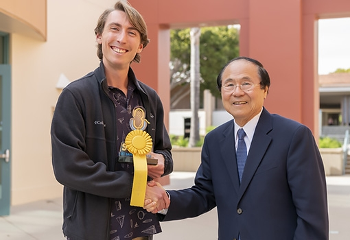 Chancellor Henry T. Yang (right) presents graduate student George Degen with first-place trophy and ribbon at the 2019 UCSB Grad Slam. Photograph by Jeff Liang