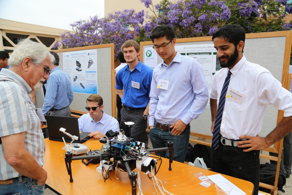 Members of Advanced Image Droning demonstrate their project to a spectator