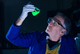 Professor Craig Hawker examines a vial of fluorescing green liquid.