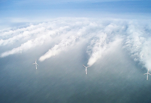 Turbines spinning in fog at an offshore wind farm reveal the wind shadows the big blades cause. Photo by Vattenfall